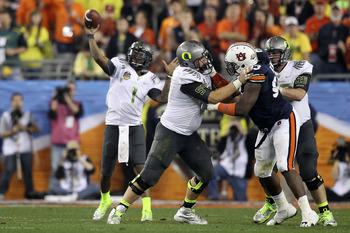 GLENDALE, AZ - JANUARY 10:  Jordan Holmes #54 of the Oregon Ducks blocks Mike Blanc #93 of the Auburn Tigers as Darron Thomas #1 of the Oregon Ducks looks to pass during the Tostitos BCS National Championship Game at University of Phoenix Stadium on Janua