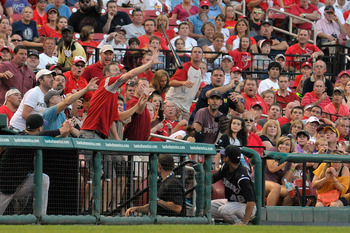 ST. LOUIS, MO - AUGUST 13: Fans react as a bat flys into the stands after Eliezer Alfonzo #55 of the Colorado Rockies lost grip of it during a game against the St. Louis Cardinals at Busch Stadium on August 13, 2011 in St. Louis, Missouri.  (Photo by Jeff