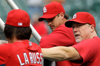 BALTIMORE, MD - JUNE 28: Hitting coach Mark McGwire #25 of the St. Louis Cardinals (R) talks with manager Tony La Russa #10 while watching batting practice before the start of their game against the Baltimore Orioles at Oriole Park at Camden Yards on June