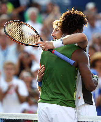 NEW YORK, NY - SEPTEMBER 01:  Juan Carlos Ferrero of Spain (R) hugs Gael Monfils of France after defeating him during Day Four of the 2011 US Open at the USTA Billie Jean King National Tennis Center on September 1, 2011 in the Flushing neighborhood of the