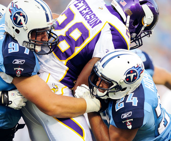 NASHVILLE, TN - AUGUST 13:  Karl Klug #97 and Chris Hope #24 of the Tennessee Titans tackle Adrian Peterson #28 of the Minnesota Vikings during a preseason exhibition game at LP Field on August 13, 2011 in Nashville, Tennessee.  (Photo by Grant Halverson/