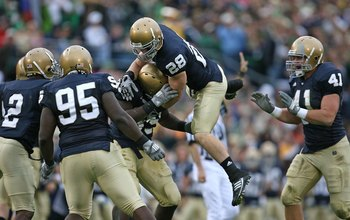 SOUTH BEND, IN - OCTOBER 03: Members of the Notre Dame Fighting Irish defense including (l-R) Darrin Walls #2, Ian Williams #95, Kyle McCarthy #28 and Scott Smith #41 celebrate a turn-over against the Washington Huskies on October 3, 2009 at Notre Dame St