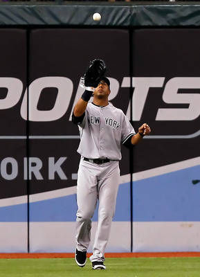 ST PETERSBURG, FL - JULY 21:  Outfielder Chris Dickerson #27 of the New York Yankees catches a fly ball against the Tampa Bay Rays during the game at Tropicana Field on July 21, 2011 in St. Petersburg, Florida.  (Photo by J. Meric/Getty Images)