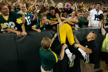 GREEN BAY, WI - SEPTEMBER 1: Vic So'oto #97 of the Green Bay Packers jumps in the stands for a Lambeau leap after scoring a touchdown on an interception during a preseason game against the Kansas City Chiefs at Lambeau Field on September 1, 2011 in Green