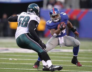 EAST RUTHERFORD, NJ - DECEMBER 19:  Ahmad Bradshaw #44 of the New York Giants runs with the ball as Trent Cole #58 of the Philadelphia Eagles defends during their game on December 19, 2010 at The New Meadowlands Stadium in East Rutherford, New Jersey.  (P