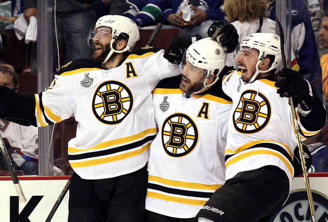 VANCOUVER, BC - JUNE 15:  Patrice Bergeron #37, Mark Recchi #28 and Brad Marchand #63 of the Boston Bruins celebrate after an open goal scored in the third period against Roberto Luongo #1 of the Vancouver Canucks during Game Seven of the 2011 NHL Stanley