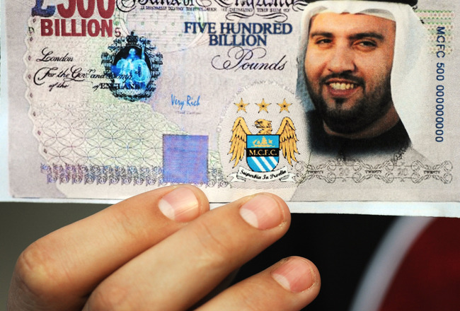 MANCHESTER, UNITED KINGDOM - SEPTEMBER 13:  A Manchester City fan holds a fake British Pound note with the face of Dr Sulaiman Al Fahim during the Barclays Premier League match between Manchester City and Chelsea at The City of Manchester Stadium on Septe
