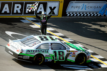 BROOKLYN, MI - AUGUST 21:  Kyle Busch, driver of the #18 Interstate Batteries Toyota, celebrates with the checkered flag after winning the NASCAR Sprint Cup Series Pure Michigan 400 at Michigan International Speedway on August 21, 2011 in Brooklyn, Michig