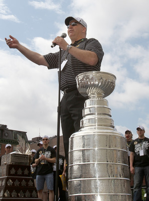 BOSTON, MA  - JUNE 18: Coach Claude Julien of the Boston Bruins raises the Stanley Cup before the start of the Stanley Cup victory parade on June 18, 2011 in Boston, Massachusetts.  (Photo by Jim Rogash/Getty Images)