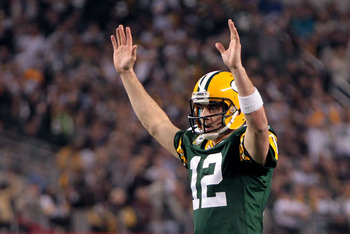 ARLINGTON, TX - FEBRUARY 06:  Aaron Rodgers #12 of the Green Bay Packers celebrates after an 8 yard touchdown pass to Greg Jennings against the Pittsburgh Steelers during Super Bowl XLV at Cowboys Stadium on February 6, 2011 in Arlington, Texas.  (Photo b