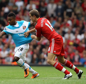LIVERPOOL, ENGLAND - AUGUST 13: Jordan Henderson of Liverpool pulls the shirt of Stephane Sessegnon of Sunderland during the Barclays Premier League match between Liverpool and Sunderland at Anfield on August 13, 2011 in Liverpool, England.  (Photo by Cli