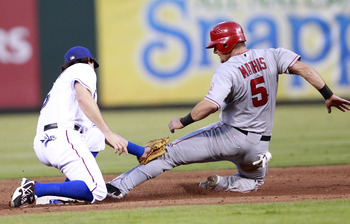 ARLINGTON, TX - AUGUST 28:  Jeff Mathis #5 of the Los Angeles Angels of Anaheim attempts to steal second base but is tagged for the out  by Ian Kinsler #5 of the Texas Rangers at Rangers Ballpark in Arlington on August 28, 2011 in Arlington, Texas. (Photo