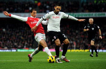 LONDON, ENGLAND - DECEMBER 04:  Marouane Chamakh of Arsenal (L) challenges Clint Dempsey of Fulham during the Barclays Premier League match between Arsenal and Fulham at the Emirates Stadium on December 4, 2010 in London, England.  (Photo by Mike Hewitt/G