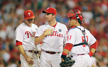 PHILADELPHIA , PA - AUGUST 26:  Roy Oswalt #44 of the Philadelphia Phillies looks on with teammates Chase Utley #26 and Carlos Ruiz #51 as he readies to leave the game in the sixth inning after giving up a grand slam to John Buck #14 (not pictured) of the