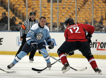 PITTSBURGH, PA - DECEMBER 31:  Paul Coffey #77 of the Pittsburgh Penguins defends against Peter Bondra #12 of the Washington Capitals during the 2011 NHL Winter Classic Alumni Game on December 31, 2010 at Heinz Field in Pittsburgh, Pennsylvania.  (Photo b