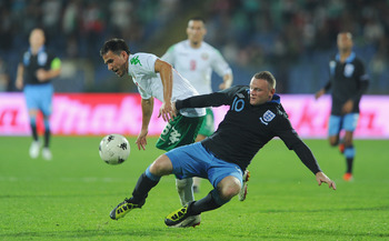 SOFIA, BULGARIA - SEPTEMBER 02: Wayne Rooney of England in action with Zhivko Milanov of Bulgaria during the EURO 2012 group G qualifying match between Bulgaria and England at the Vasil Levski National Stadium on September 2, 2011 in Sofia, Bulgaria.  (Ph