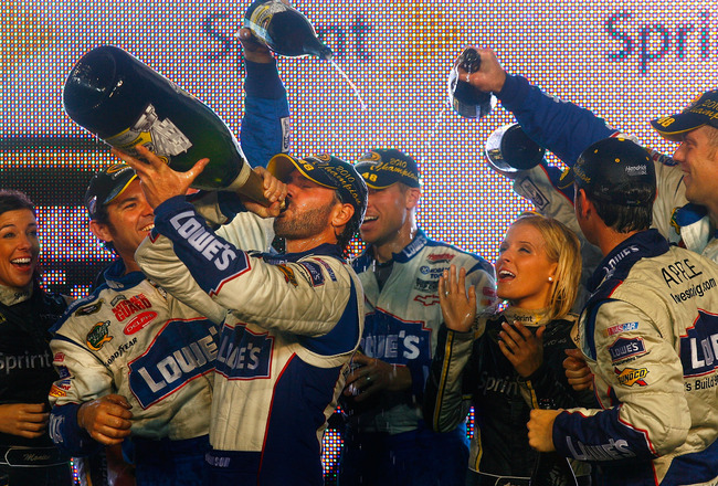 HOMESTEAD, FL - NOVEMBER 21:  Jimmie Johnson (L), driver of the #48 Lowe's Chevrolet, drinks champagne in celebration with teammates after winning his fifth consecutive NASCAR Sprint Cup championship following the Ford 400 at Homestead-Miami Speedway on N
