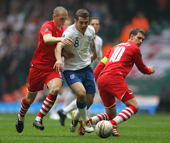 CARDIFF, WALES - MARCH 26:  Jack Wilshere of England takes the ball past Aaron Ramsey (R) and Andrew Crofts of Wales during the UEFA EURO 2012 Group G qualifying match between Wales and England at the Millennium Stadium on March 26, 2011 in Cardiff, Wales