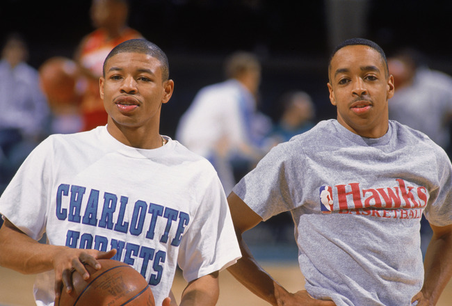 CHARLOTTE, NC - 1989:  Mugsy Bogues #1 of the Charlotte Hornets stands on the court with Spud Webb #4 of the Atlanta Hawks before an NBA game at Charlotte Colesium in 1989. (Photo by Jim Gund/Getty Images)