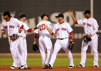BOSTON, MA - SEPTEMBER 3: (L to R) Darnell McDonald #54, Dustin Pedroia #15, Marco Scutaro #10, Mike Aviles #3, and Carl Crawford #13 of the Boston Red Sox slap high fives following their game against the Texas Rangers at Fenway Park on September 3, 2011