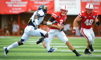 LINCOLN, NE - SEPTEMBER 3: Taylor Martinez #3 of the Nebraska Cornhuskers tries to slip past Kadeem Wise #5 of the Chattanooga Mocs during their game at Memorial Stadium September 3, 2011 in Lincoln, Nebraska.  (Photo by Eric Francis/Getty Images)