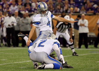 Former Detroit Lions punter Nick Harris holds for Jason Hanson's field goal attempt.