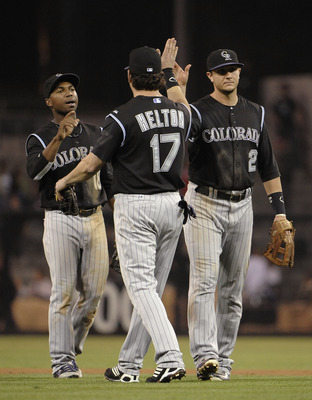 SAN DIEGO, CA - SEPTEMBER 2:  Jonathan Herrera #18 of the Colorado Rockies high-fives with Todd Helton #17 and Troy Tulowitzki #2 after a win against the San Diego Padres at Petco Park on September 2, 2011 in San Diego, California. The Rockies won 3-0.  (