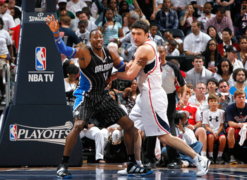 ATLANTA, GA - APRIL 28:  Dwight Howard #12 of the Orlando Magic battles for position in the paint against Zaza Pachulia #27 of the Atlanta Hawks during Game Six of the Eastern Conference Quarterfinals in the 2011 NBA Playoffs at Philips Arena on April 28,