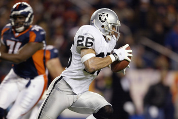 DENVER, CO - NOVEMBER 11:  Safety Rod Woodson #26 of the Oakland Raiders intercepts a pass intended for Clinton Portis of the Denver Broncos and returns it 98 yards for a touchdown in the first quarter of Monday Night Football November 11, 2002, at Mile H