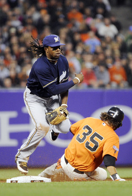 SAN FRANCISCO, CA - JULY 22: Rickie Weeks #23 of the Milwaukee Brewers gets his throw off to complete the double-play, avoiding the slide of Brandon Crawford #35 of the San Francisco Giants in the fifth inning during an MLB baseball game at AT&T Park July