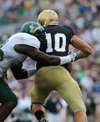 SOUTH BEND, IN - SEPTEMBER 03:  Dayne Crist #10 of the Notre Dame Fighting Irish is sacked by Julius Forte #54 of the University of South Florida Bulls at Notre Dame Stadium on September 3, 2011 in South Bend, Indiana.  (Photo by Jonathan Daniel/Getty Ima