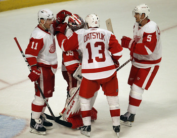 CHICAGO, IL - APRIL 10: (L-R) Danny Cleary #11, Jimmy Howard #35, Pavel Datsyuk #13 and Nicklas Lidstrom #5 of the Detroit Red Wings celebrate a win over the Chicago Blackhawks at the United Center on April 10, 2011 in Chicago, Illinois. The Red Wings def