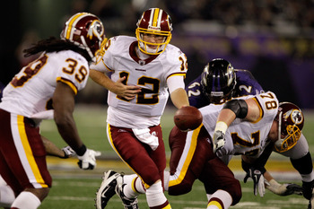 BALTIMORE, MD - AUGUST 25:  Quarterback John Beck #12 of the Washington Redskins hands the ball off to running back Tim Hightower #39 during a preseason game against the Baltimore Ravens at M&T Bank Stadium on August 25, 2011 in Baltimore, Maryland.  (Pho