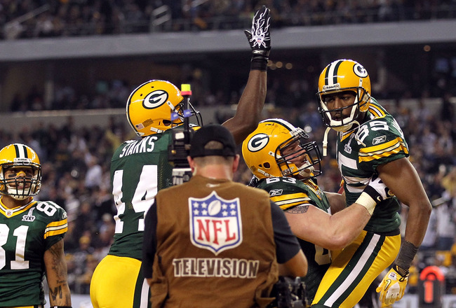 ARLINGTON, TX - FEBRUARY 06:  Greg Jennings #85 of the Green Bay Packers celebrates with teammates Scott Wells #63 and James Starks #44 after catching a 21 yard touchdown against the Pittsburgh Steelers during Super Bowl XLV at Cowboys Stadium on February