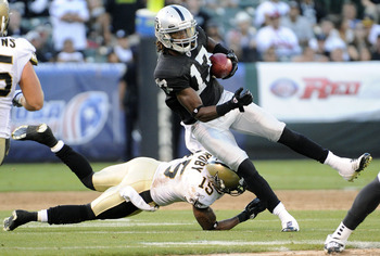 OAKLAND, CA - AUGUST 28: Denarius Moore #17 of the Oakland Raiders returning a punt is tripped up by Courtney Roby #15 of the New Orleans Saints in the third quarter during an NFL pre-season football game at the O.co Coliseum August 28, 2011 in Oakland, C