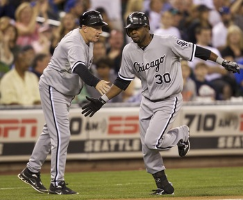 SEATTLE, WA - AUGUST 27: Alejandro De Aza #30 of the Chicago White Sox is congratulated by Chicago White Sox third base coach Jeff Cox on his way to home plate during a game against the Seattle Mariners at Safeco Field on August 27, 2011 in Seattle, WA. T
