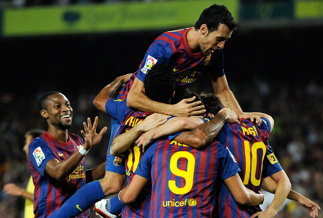 BARCELONA, SPAIN - AUGUST 29:  Sergio Busquets of FC Barcelona jumps over his teammates as they celebrates after Lionel Messi scored his fourth team's goal during the La Liga match between FC Barcelona and Villarreal CF at Camp Nou on August 29, 2011 in B