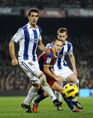 BARCELONA, SPAIN - DECEMBER 12:  Andres Iniesta of Barcelona (C) challenges for the ball with Xabier Prieto (L) and David Zurutuza of Real Sociedad during the La Liga match between Barcelona and Real Sociedad at Camp Nou Stadium on December 12, 2010 in Ba