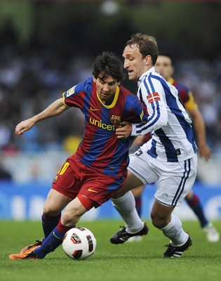 SAN SEBASTIAN, SPAIN - APRIL 30:  Lionel Messi of FC Barcelona (L) fights for the ball against Diego Rivas of Real Sociedad during the La Liga match between Real Sociedad and Barcelona at Estadio Anoeta on April 30, 2011 in San Sebastian, Spain. Real Soci
