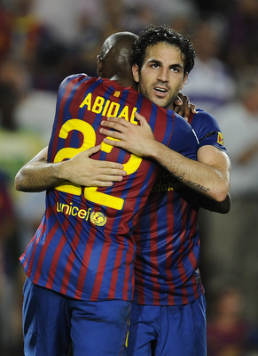 BARCELONA, SPAIN - AUGUST 29:  Cesc Fabregas of FC Barcelona celebrates with his teammate Eric Abidal after scoring his second team's goal during the La Liga match between FC Barcelona and Villarreal CF at Camp Nou on August 29, 2011 in Barcelona, Spain.