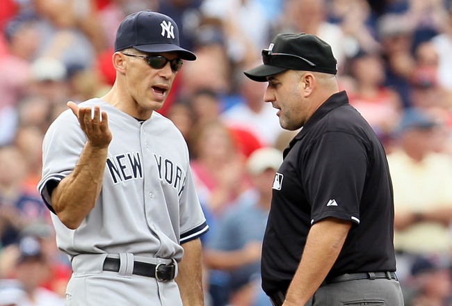 BOSTON, MA - AUGUST 06: Manager Joe Girardi #28 of the New York Yankees discusses a call with second base umpire Jeff Kellogg in the third inning against the Boston Red Sox  on August 6, 2011 at Fenway Park in Boston, Massachusetts.  (Photo by Elsa/Getty