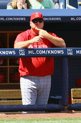NEW YORK, NY - AUGUST 11: Manager Mike Scioscia #14 of the Los Angeles Angels of Anaheim gives signals during game action against the New York Yankees at Yankee Stadium on August 11, 2011 in the Bronx borough of New York City. (Photo by Andy Marlin/Getty