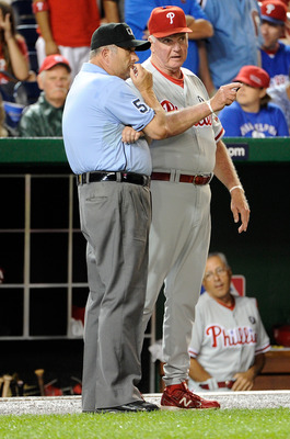 WASHINGTON, DC - AUGUST 19:  Manager Charlie Manuel of the Philadelphia Phillies talks with umpire crew chief Dale Scott #5 during a rain delay in the game against the Washington Nationals at Nationals Park on August 19, 2011 in Washington, DC.  (Photo by