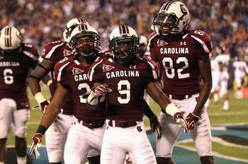 CHARLOTTE, NC - SEPTEMBER 03:  Sharrod Golightly #9 of the South Carolina Gamecocks celebrates with teammates after returning a kick for a touchdown against the East Carolina Pirates during their game at Bank of America Stadium on September 3, 2011 in Cha