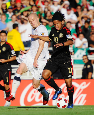 PASADENA, CA - JUNE 25:  Giovanni Dos Santos #10 of Mexico and Michael Bradley #4 of the United States battle for the ball during the 2011 CONCACAF Gold Cup Championship at the Rose Bowl on June 25, 2011 in Pasadena, California.  (Photo by Kevork Djansezi