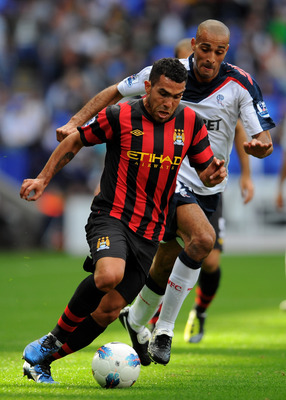 BOLTON, ENGLAND - AUGUST 21:  Carlos Tevez  of Manchester City tussles for posession with Darren Pratley of Bolton Wanderers during the Barclays Premier League match between Bolton Wanderers and Manchester City at the Reebok Stadium on August 21, 2011 in