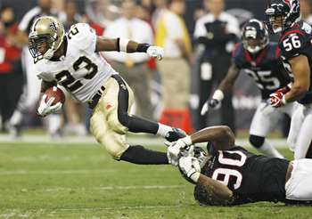 HOUSTON - AUGUST 20:  Running back Pierre Thomas #23 of the New Orleans Saints is tackled by linebacker Mario Williams #90 at Reliant Stadium on August 20, 2011 in Houston, Texas.  (Photo by Bob Levey/Getty Images)