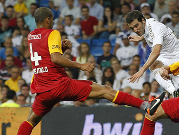 MADRID, SPAIN - AUGUST 24: Gonzalo Higuain of Real Madrid shoots on goal between Tomas Ujfalusi (R) and Felipe Melo of Galatasaray during the Santiago Bernabeu Trophy match between Real Madrid and Galatasaray at Estadio Santiago Bernabeu on August 24, 201