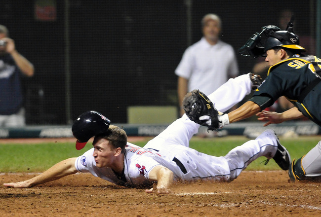 CLEVELAND, OH - AUGUST 31: Cord Phelps #35 of the Cleveland Indians slides safely into home for the winning run as catcher Kurt Suzuki #8 of the Oakland Athletics tries to make the tag during the sixteenth inning at Progressive Field on August 31, 2011 in
