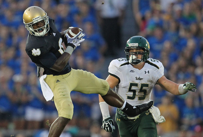 SOUTH BEND, IN - SEPTEMBER 03: Theo Riddick #6 of the Notre Dame Fighting Irish leaps to catch a pass in front of Michael Lanaris #55 of the University of South Florida Bulls at Notre Dame Stadium on September 3, 2011 in South Bend, Indiana. (Photo by Jon